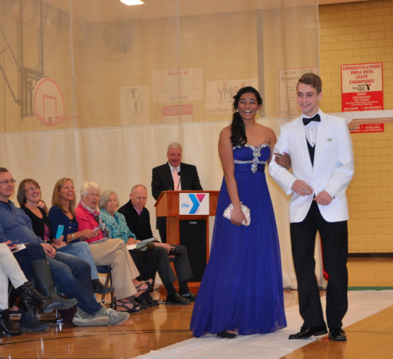 Senior Jeevana Pakanati (left) and junior Ryan Goldsher pose on the runway at the Prom Fashion Show. Prom-inspired clothing was modeled by 43 high school students. Photo by Anna Hirshman