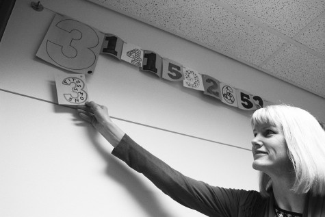 Math teacher Karen Fitzsimons poses in front of decorative numbers of pi in the Math Resource Center. Fitzsimons was a proponent for the establishment of Pi Day celebrations in the math department last year.