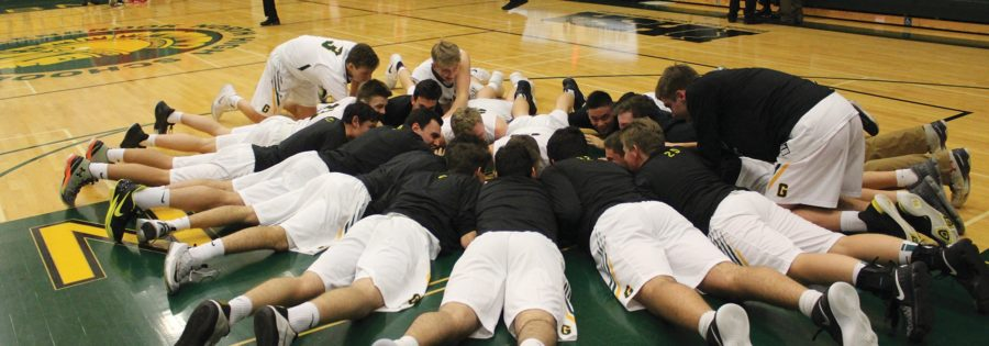 As a pregame routine, the boys basketball team huddles in preparation for its season opener against Niles West, a 67-64 win on Nov. 20 in which senior Kellen Witherell scored 16 points. Photo by Hope Mailing