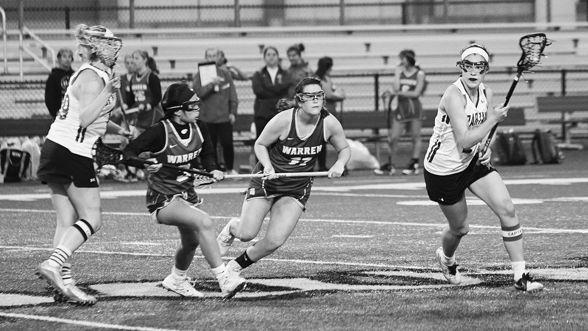 Senior Naomi Lutz (right) plays offense in the girls lacrosse game against Warren Township on May 14. Next year, she plans to attend the Massachusetts Institute of Technology as a lacrosse commit. Photo by Richard Chu.