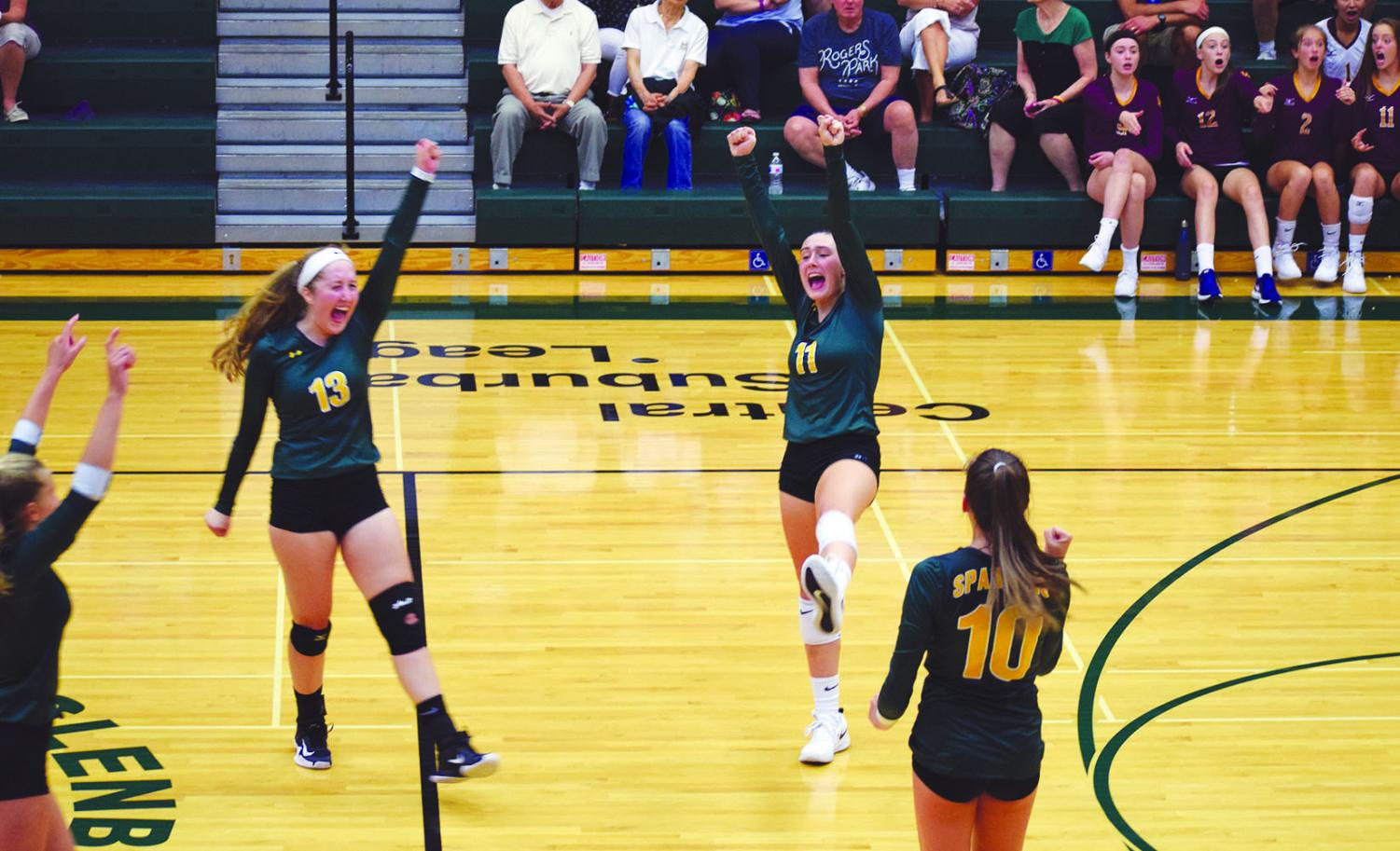 Junior Casey Brown (center) celebrates with her teammates after a point is scored against Loyola Academy on Aug. 29. This has been Brown's first year with the Spartans, helping them to a record of 12-5 as of Sept. 24. Photo by Grace Chatas