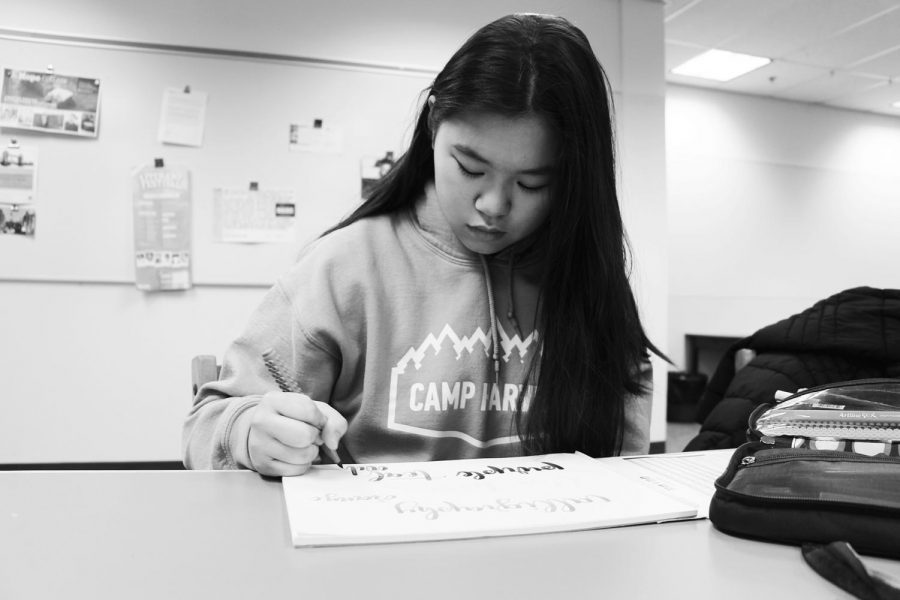 Junior Cameron Fong concentrates as she practices writing calligraphy. Fong uses calligraphy to create  cards and vinyl stickers. She also has an Instagram account where she features her work.
