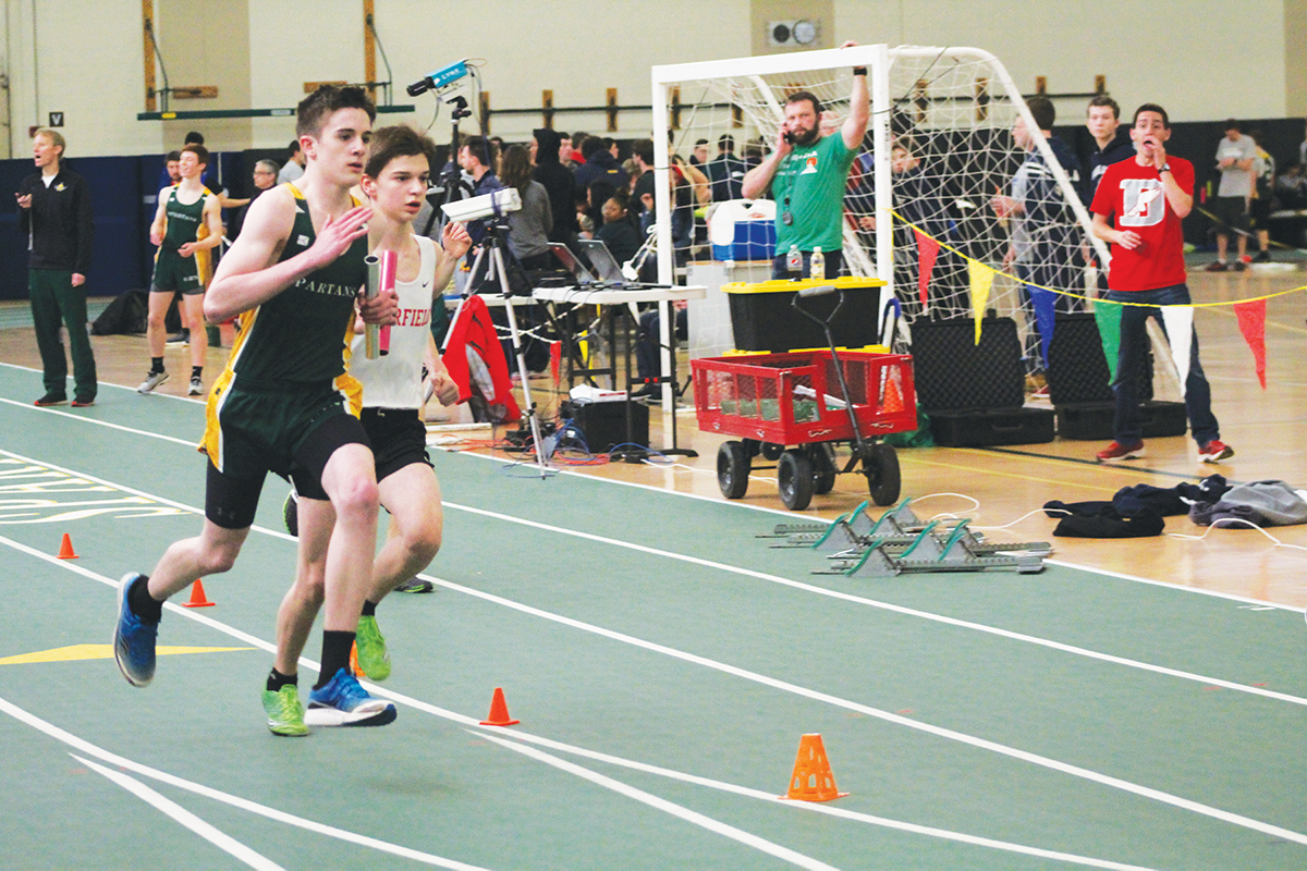 Freshman Patrick Herbst runs a relay at the CSL indoor conference meet on March 15. Beginning with the class of 2022, completing both indoor and outdoor track will not count as two sports towards the 12-Season Athlete Award. For all older athletes, completing both sports counts as two credits towards the award. Photo by Karina Belotserkovskiy