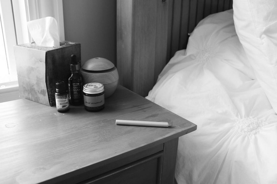 An essential oil vape lies on a nightstand with essential oils and a  diffuser, as essential oils are marketed to help people sleep.
