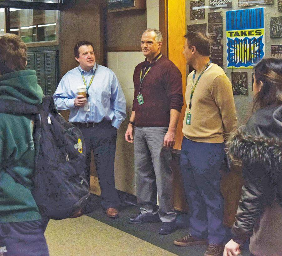 John Finan (left), Scott Williams (middle) and Ed Solis (right) converse as students pass by during block 2-3. On Dec. 10, Finan announced that he plans to step down as principal after five years in the role. Photo by Haley Sandlow