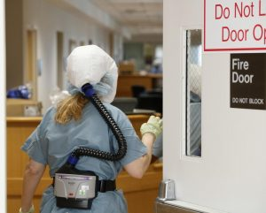 A Glenbrook Hospital COVID-19 clinical team member wears personal protective equipment including a powered, air-purifying respirator, also known as a PAPR. The clinical team member entered the nurses' station where she was to be covered with a protective gown before caring for a patient. Photo courtesy of Jon Hillenbrand, NorthShore University HealthSystem