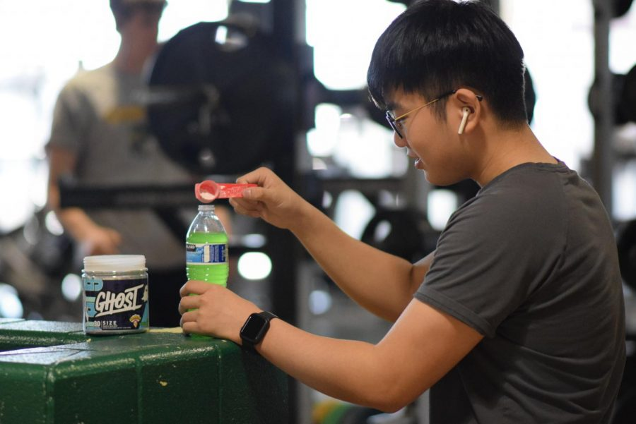 Junior Frank Min dumps muscle-building powder into his water during a workout after school. The pictured powder does not contain added caffeine, unlike other supplements. Photo by Natalie Sandlow