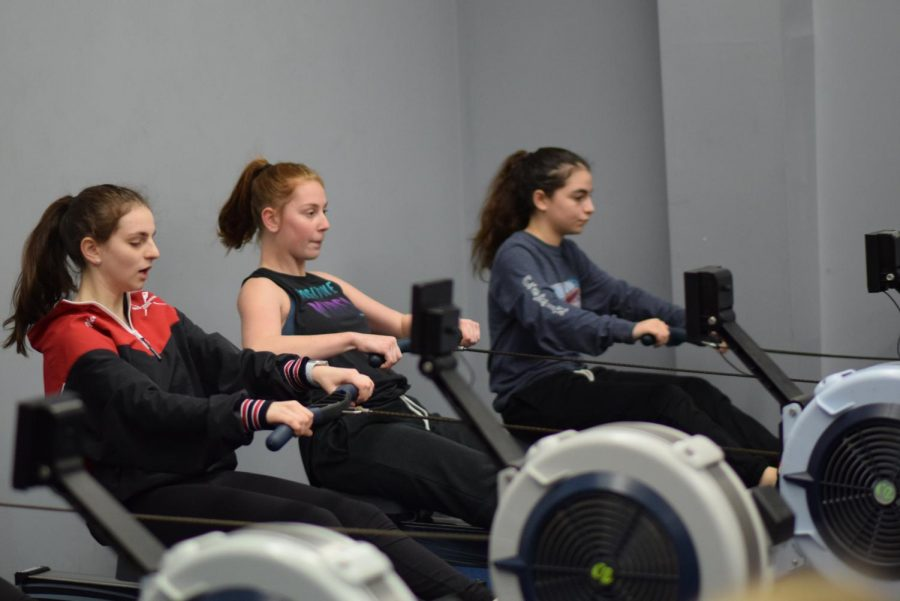 Sophomore Abby Schyman (center) and junior Nikki Nemerson (left) practice in the Dammrich Rowing Center in Skokie on March 4. North Suburban Crew uses the Dammrich Rowing Center when the weather does not permit the team to practice on the Skokie Lagoons. Photo by Natalie Sandlow