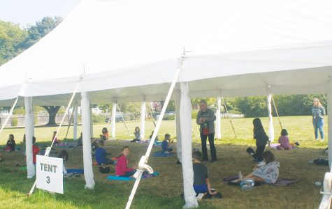 Students at Greenbriar Elementary School sit under one of the tents outside the school taking a