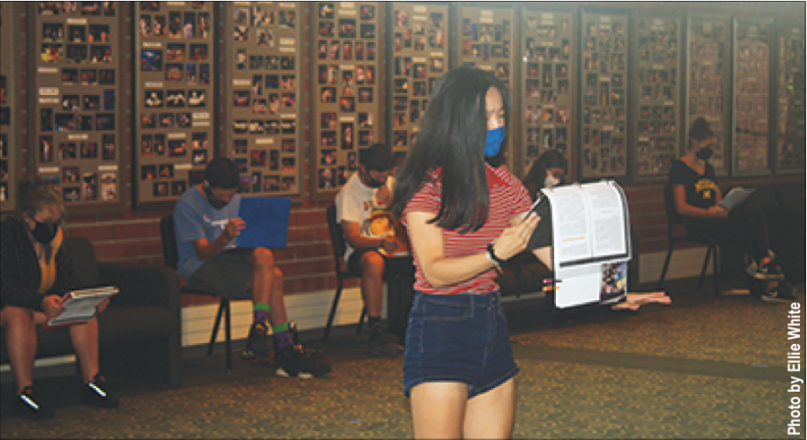 """Junior Claire Chang reads her lines during a rehearsal in the CPA lobby. """"The Laramie Project"""" is scheduled to be broadcast at 7 p.m. on Oct. 22, Oct. 23 and Oct. 24. Photo by Ellie White"""