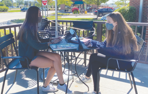 In a staged photo, yearbook Editors-in-Chief Ceci Santellano (left) and Jamie Resis talk. The yearbook is planned to look different this year compared to previous years due to COVID-19. Photo by Rachel Cha