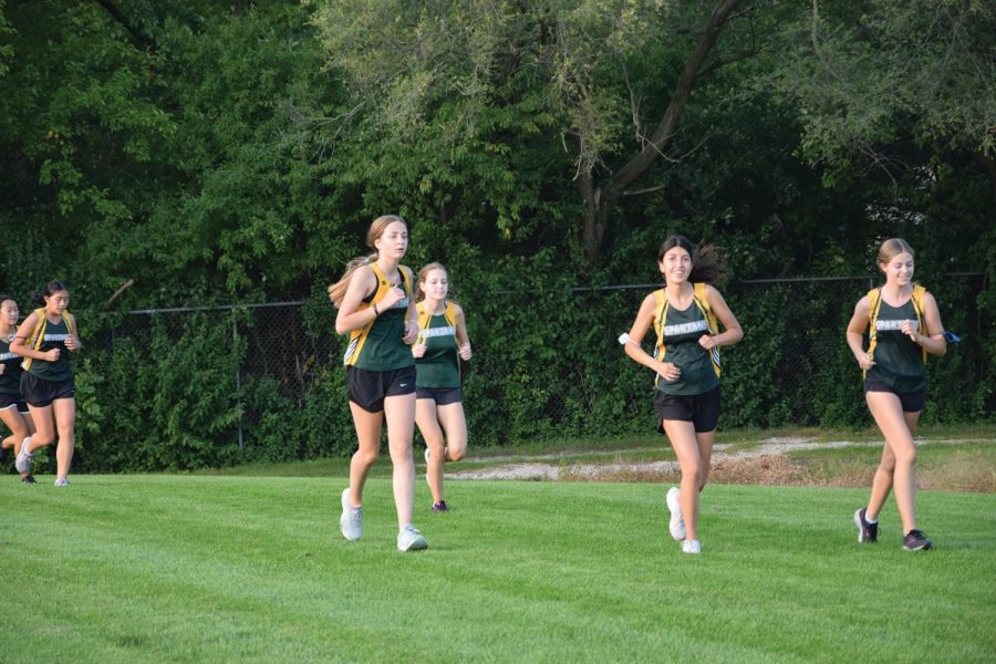 JV cross country runners round a turn of their 3-mile race at Glenbrook North on Sept. 15. Cross country teams have implemented new safety protocols to prevent the spread of COVID-19. Photo by Natalie Sandlow