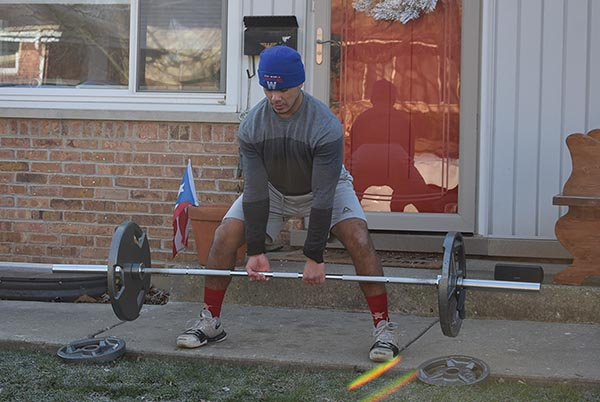 Senior Drake Marquez lifts weights outside of his house on the morning of Saturday, Dec. 5. Due to his right leg injury, Marquez needed plates in his leg and was disqualified from his Marines program. Photo by Natalie Sandlow
