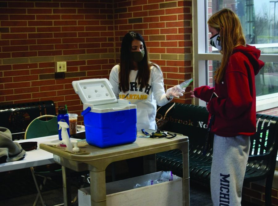 Junior Kate Rassin (right) hands her saliva sample to athletic trainer Humaira Baig on Dec. 8. Athletes in girls basketball, boys basketball and boys swimming can opt in for one-on-one training that requires two saliva tests per week. Photo by Natalie Sandlow