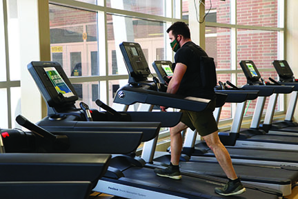 While wearing a 40-lb vest, P.E. teacher Justin Weiner trains in the fitness center on March 19 for his Mount Kilimanjaro climb. Photo by Alex Garibashvily