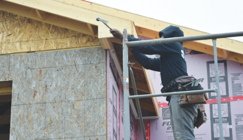 A Habitat for Humanity construction team member builds a home located in Waukegan. The construction for this home began in April, and is scheduled to be completed this summer. Photo by Natalie Sandlow