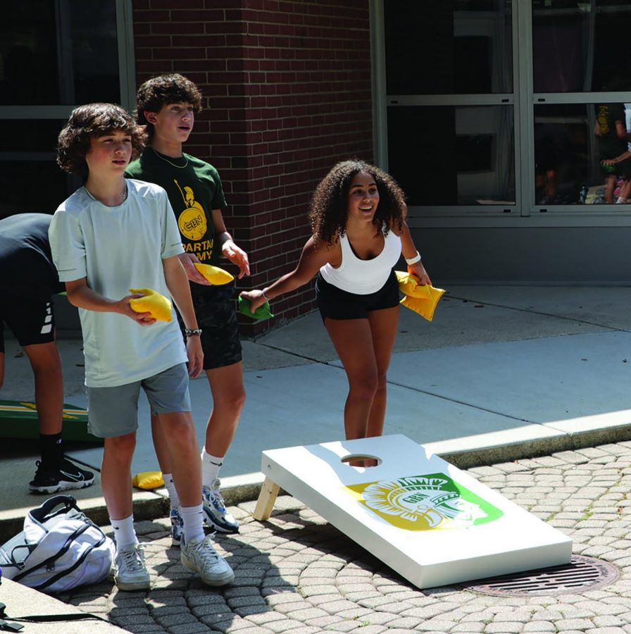 During lunch, students play corn hole outside in the student mall. Students should take advantage of opportunities to engage in activities and events to elevate school mindset. Photo by Alex Garibashvily