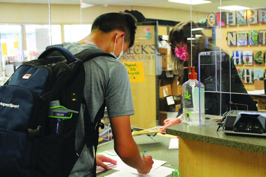 In the bookstore, freshman Ricky Gu picks up Born A Crime by Trevor Noah for his English class. If a students book has a gold sticker, it must be returned at the end of the school year. Photo by Claire Satkiewicz