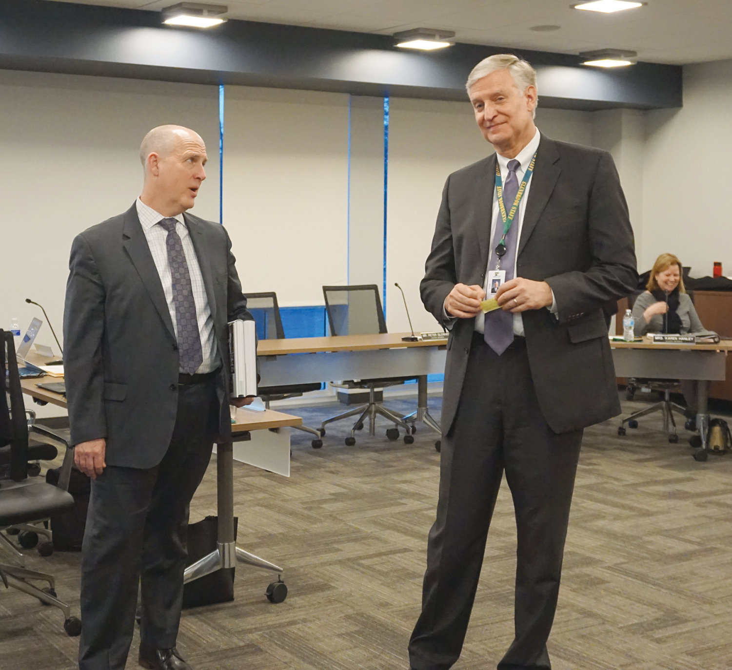 At a District #225 board meeting, newly hired superintendent Charles Johns (left) and current superintendent Mike Riggle exchange greetings. Johns is scheduled to assume this position on July 1. Photo by Andreea Sabau