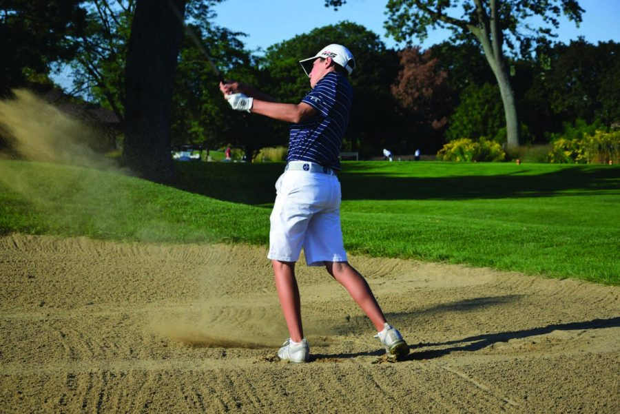 Freshman Jason Gordon shoots from a sand trap at Sportsman's Country Club at practice on Friday, Sept. 6. Gordon was one of two freshmen chosen to play on the varsity team this year. Photo by Natalie Sandlow