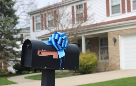 A blue bow supplied by Buffalo Grove resident Robin Fields is tied onto Northbrook resident Kathy Moran's mailbox. Fields started the blue bow movement to acknowledge the work of all first responders and frontline workers. Photo by Sarah Boeke