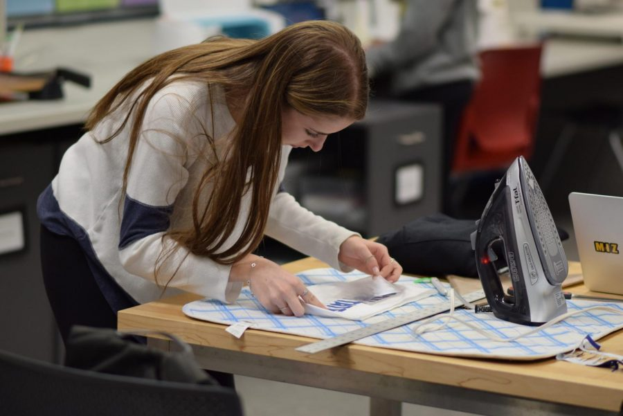 Senior Sarah Glass leans down as she works on a piece of customized apparel. In 2019, she and seniors Julia Foster and Sophie Rogoff co-founded Hardcore College, an Instagram account that sells customized clothing.