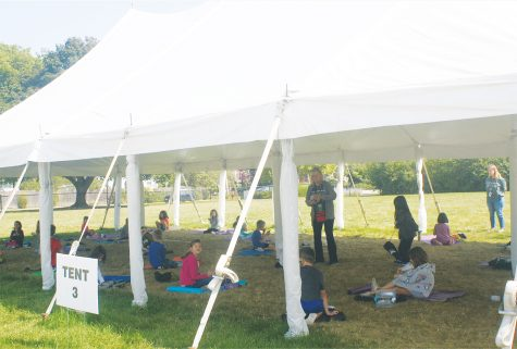 """Students at Greenbriar Elementary School sit under one of the tents outside the school taking a """"mask break"""" while eating lunch. Students were given the choice between learning remotely or in person. Photo by Ellie White"""