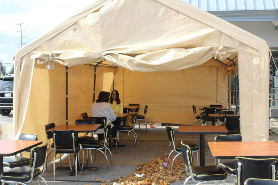 Two+customers+dine+in+a+tent+in+the+parking+lot+outside+Once+Upon+a+Grill.+Once+Upon+a+Grill+installed+a+tent+to+continue+providing+a+dine-in+option+for+costumers+while+the+weather+gets+colder.+Photo+by+Brooke+Falk