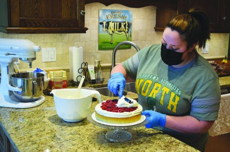 Laura Ruesch, executive assistant in the Deans' Office, frosts a white cake using whipped cream frosting for an order. Ruesch began running her baking business from her kitchen in 2014. Photo by Natalie Sandlow