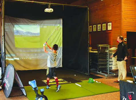 During a private lesson on April 3, Michael Wenzel, director of instruction at Northbrook Golf Academy, observes a player using a TrackMan Golf Simulator at the Chalet at Meadowhill Park. The simulator will be moved to Heritage Oaks once the renovations are complete. Photo by Natalie Sandlow