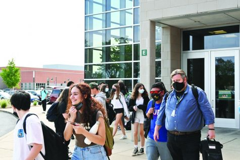 Junior Elani Torres takes off her mask while leaving the building after school. Students are encouraged but not required to maintain a proper social distance of three feet when unmasked and outside. Photo by Saruul-Erdene Jagdagdorj