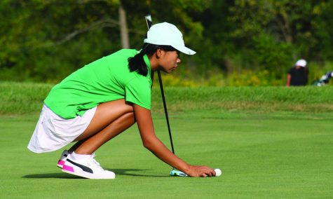 Prior to putting, freshman Kacie Moon places her ball during practice on Thursday, Sept. 2. Moon shot 31 in a match against Niles West on Aug. 24, breaking the previous school record. Photo by Jiya Sheth